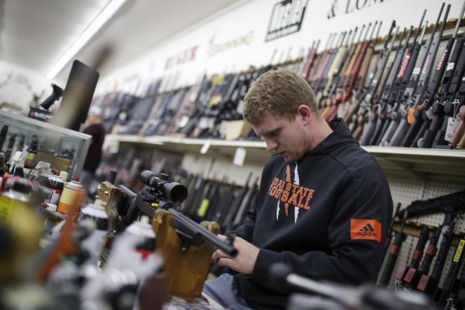 Un homme inspecte une arme à feu au magasin Ross Coin and Gun,à Idaho Falls, dans l'Idaho, le 16 mars.