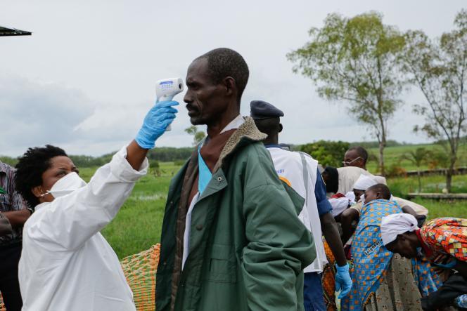 Alors que s'étend la pandémie de Covid-19, une soignante prend la température d'un homme à titre préventif à Gatumba (Burundi), à la frontière avec la République démocratique du Congo, le 18 mars.