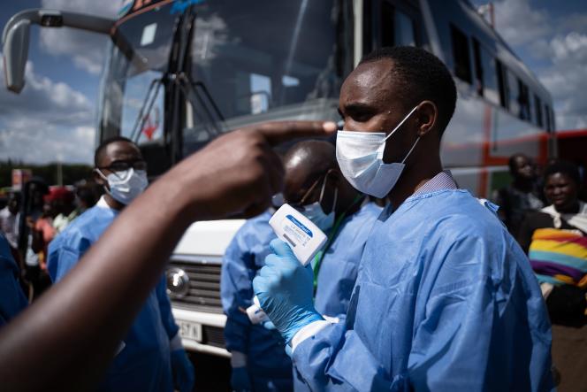 Un membre du Rwanda Biomedical Center (RBC) contrôle les passagers d'une gare pour freiner la propagation du coronavirus, à Kigali, le 22 mars.