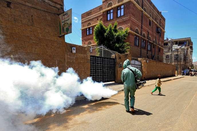Un agent du gouvernement traite les rues de la capitale yéménite, Sanaa, dans le but de contenir la propagation de l'épidémie de Covid-19, le 23 mars 2020.