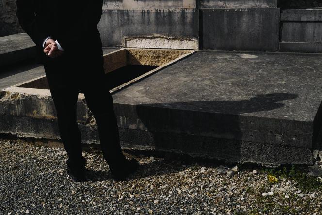 Un membre de la famille se recueille devant le cercueil d'une dame décédée du coronavirus, lors de son l'inhumation dans le caveau familial au cimetiere de Ruffieux dans l'Ain, le 19 mars 2020. Lucas Barioulet