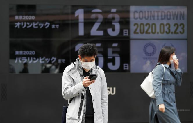 Des passants devant un compte à rebours des jours restants jusqu'aux Jeux olympiques et paralympiques de Tokyo 2020 à Tokyo, le 23 mars.