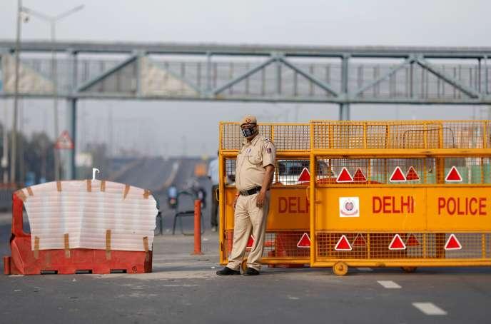 A New Delhi, le 23 mars, un policier installe des barrières en application des mesures de confinement.