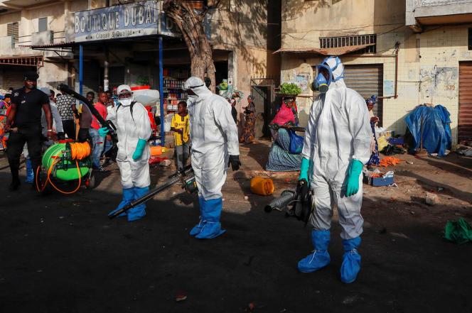 Les membres des services d'hygiène désinfectent les abords d'unmarché pour tenter d'arrêter la propagation du coronavirus, à Dakar (Sénégal), le 22 mars.