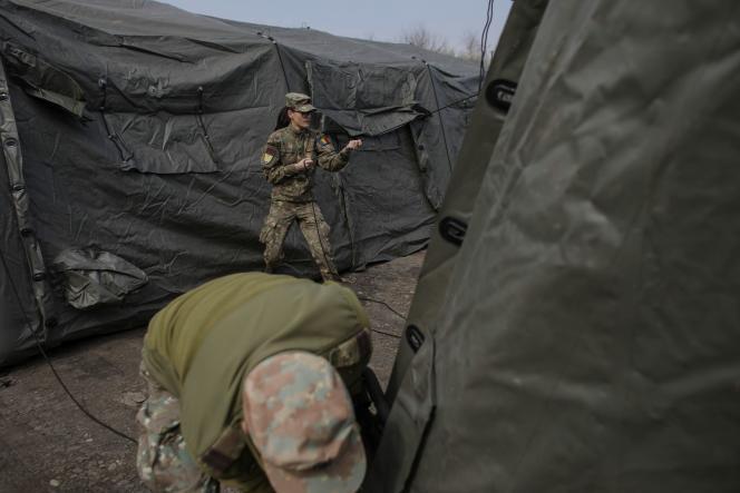 Des militaires érigent des tentes pour un hôpital militaire mobile destiné aux malades du Covid-19, près de Bucarest, le 20 mars.