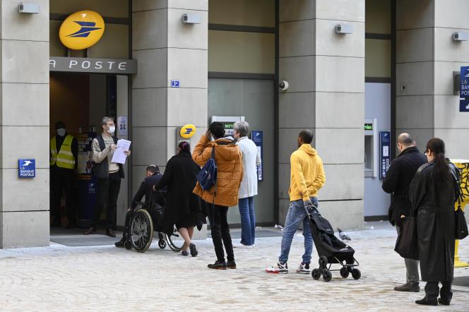 Des gens font la queue devant un bureau de La Poste, à Strasbourg, le 17 mars.
