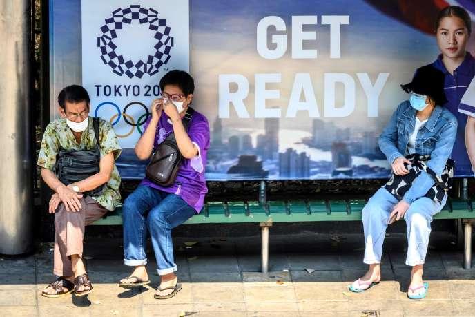 Devant une publicité pour les Jeux olympiques, à Tokyo, le 23 mars.