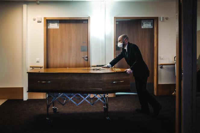 Un employé des pompes funèbres transporte le cercueil d'une dame décédée dans la nuit du coronavirus dans un Ehpad, à Paris, le 18 mars 2020.