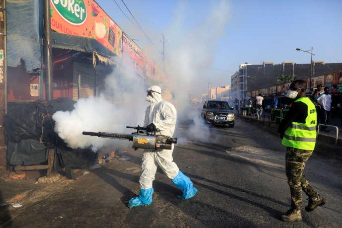 Un membre des services d'hygiène désinfecte un marché à Dakar, le 22 mars 2020.