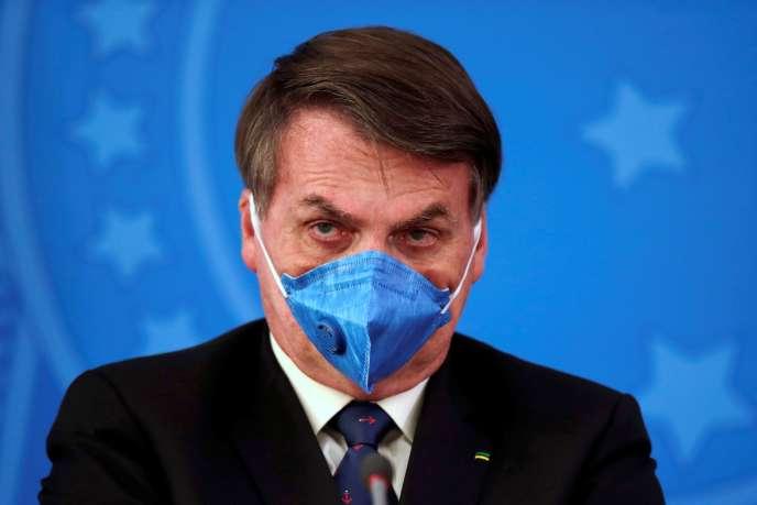 Le président brésilien Jair Bolsonaro, avec un masque de protection, lors d'un point presse sur le coronavirus, à Brasilia, le 20 mars.