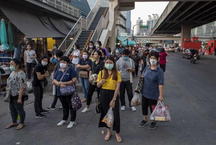 Des voyageurs attendent leur train à Bangkok, Thaïlande, le 24 mars.