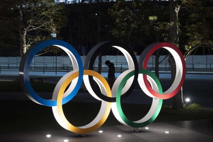 Les anneaux olympiques devant le Stade national de Tokyo, le 24 mars.