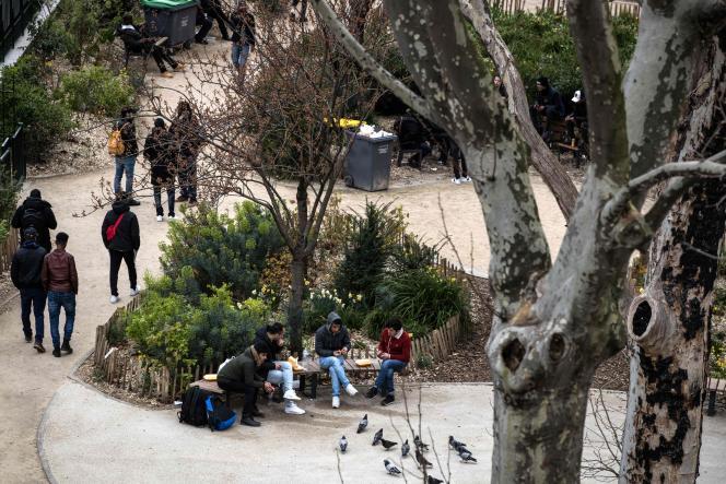 Migrants dans un parc parisien, le 16 mars.