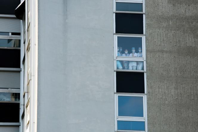 Des soignants suivent, de leur fenêtre, la visite d'Emmanuel Macron à l'hôpital Emile-Muller, à Mulhouse, mercredi 25 mars 2020.