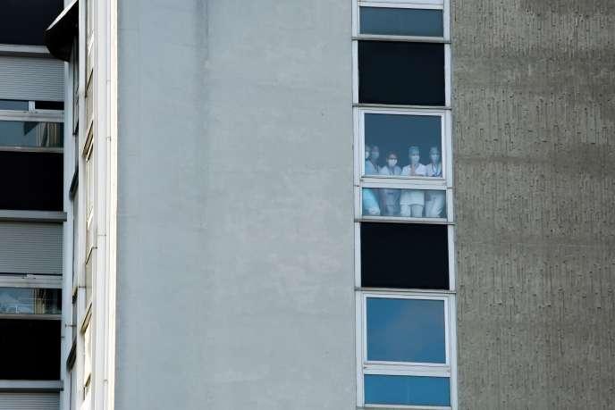 Des soignants suivent, de leur fenêtre, la visite d'Emmanuel Macron à l'hôpital Emile-Muller, à Mulhouse, mercredi 25 mars.