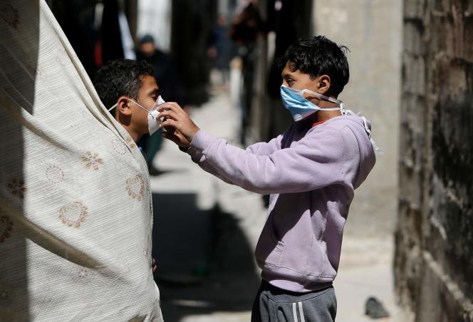 Un enfant ajuste le masque d'un autre enfant, dans le camp al-Shati, à Gaza, le 25 mars.