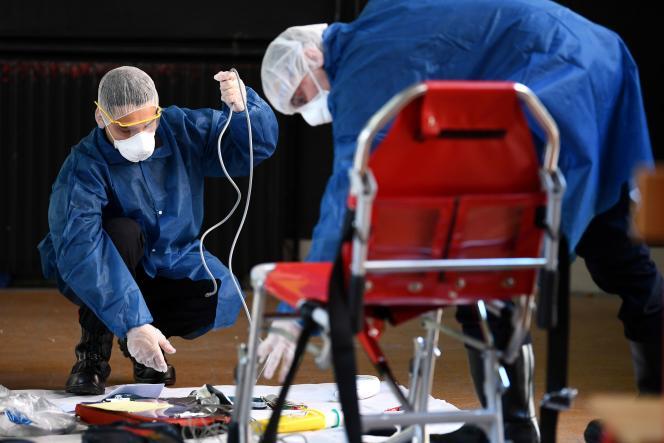 Des pompiers désinfectent du matériel après une intervention sur un patient atteint du Covid-19, le 24 mars à Paris.