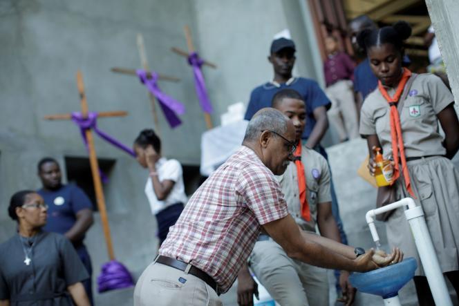 Un homme se lave les mains à la sortie d'une église le 15 mars à Port-au-Prince.