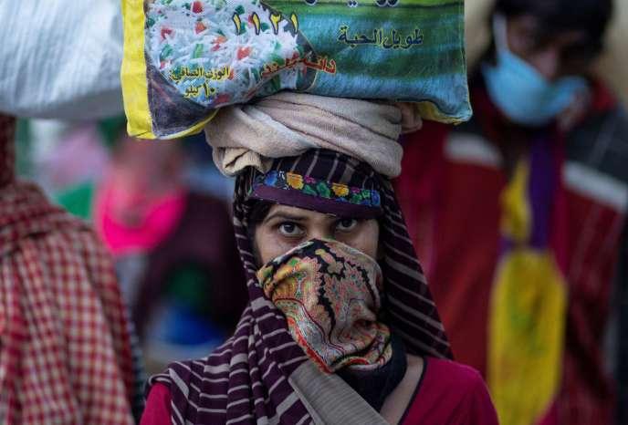 Unetravailleuse migrante porte ses affaires sur la route de son village à New Delhi, le 26 mars.