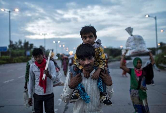 Un travailleur migrant porte son fils sur la route de son village à New Delhi, le 26 mars.