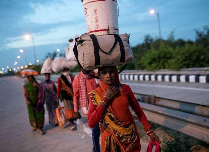 Une travailleuse migrante porte ses affaires sur la route de New Delhi à son village, le 26 mars.