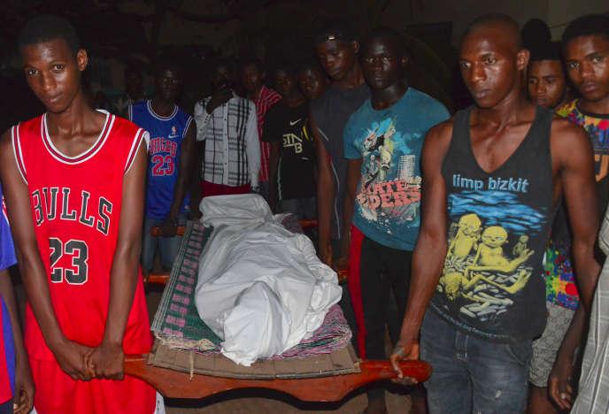 Des proches portent le corps d'un homme décédé lors d'affrontements entre la police et des manifestants à Conakry, le 22 mars 2020.