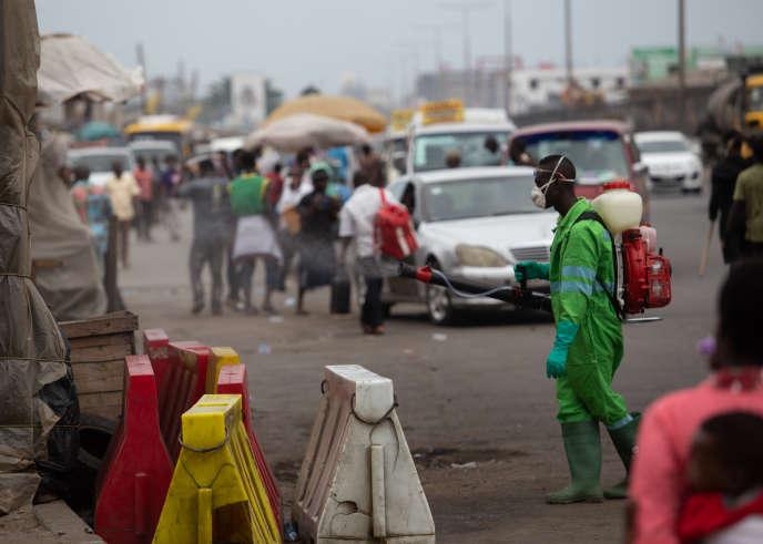 Désinfection des rues du marché à Accra, devant une file de VTC, le 23 mars 2020.