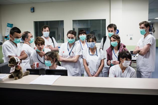 19 h 15. L'équipe du jour rend compte de la situation des patients à l'équipe de nuit, grâce à un système de visioconférence.