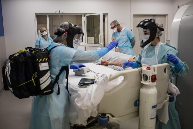 6 h 04. Le réanimateur de garde, avec l'aide d'une infirmière et d'une aide-soignante, transportent le patient en suspicion jusqu'au service de réanimation.