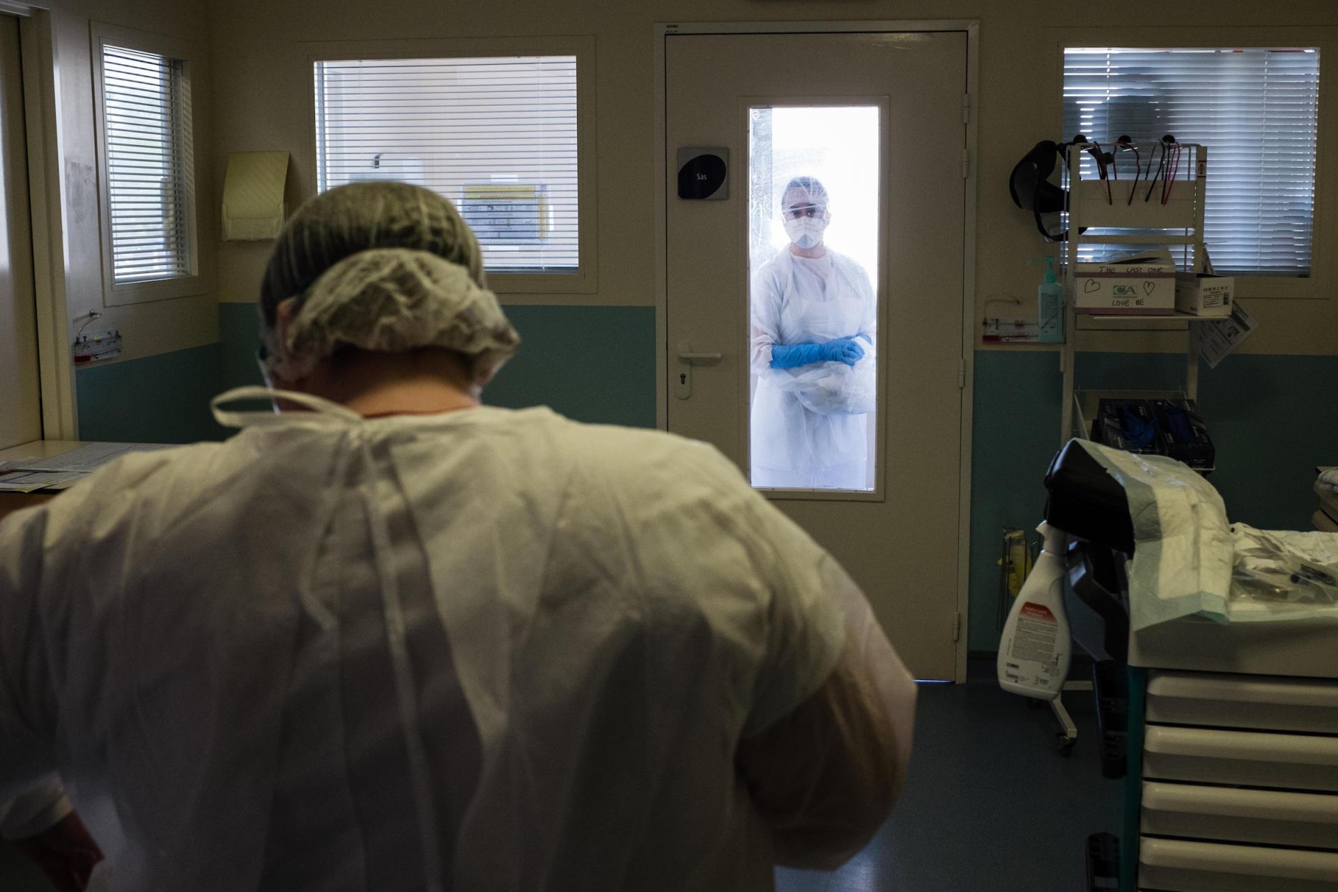 17 heures. Une infirmière attend dans le sas de transfert pressurisé sa collègue aide-soignante, pour soigner un patient atteint du Covid-19.
