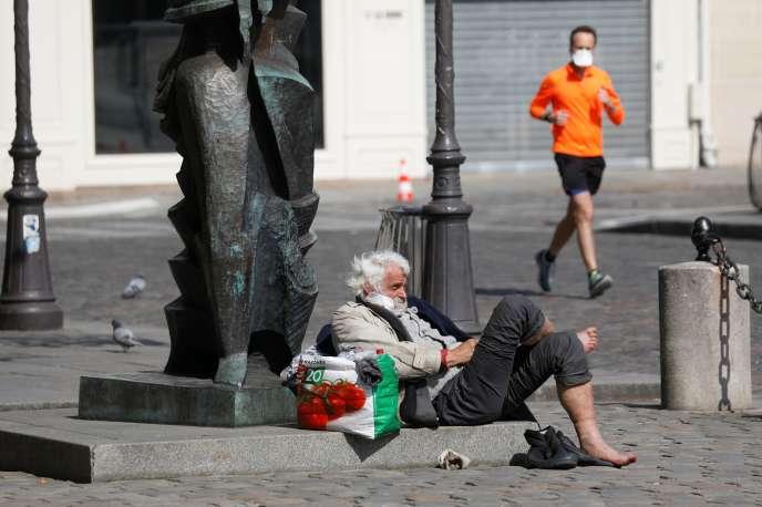 Un joggeur, portant un masque de protection, passe à côté d'un sans-abri dans une rue de Paris, le 27 mars.