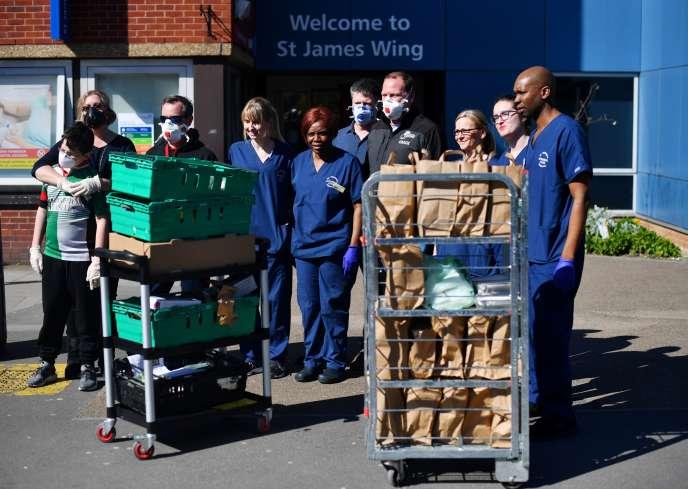 Infirmiers, médecins et volontaires reçoivent des repas pour les patients, à l'hôpital St Georges à Londres, le 23 mars.