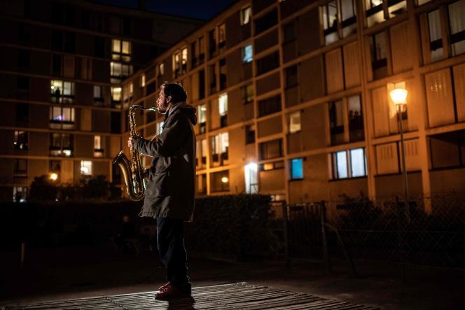 Un saxophoniste offre un concert improvisé dans un quartier de Paris, où les personnes vivent confinées depuis dix jours.
