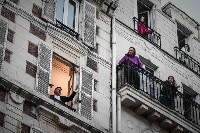 Des personnes confinées chez elle, à Paris, le 26 mars.