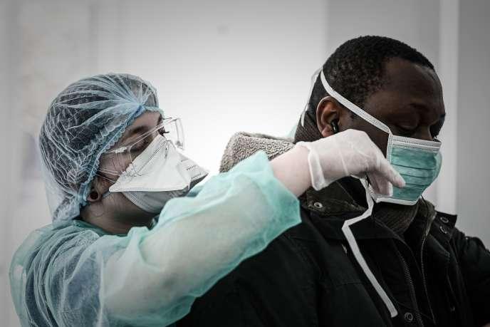 Une soignante équipe d'un masque un patient soupçonné d'être atteint du Covid-19, le 27 mars, à Paris.