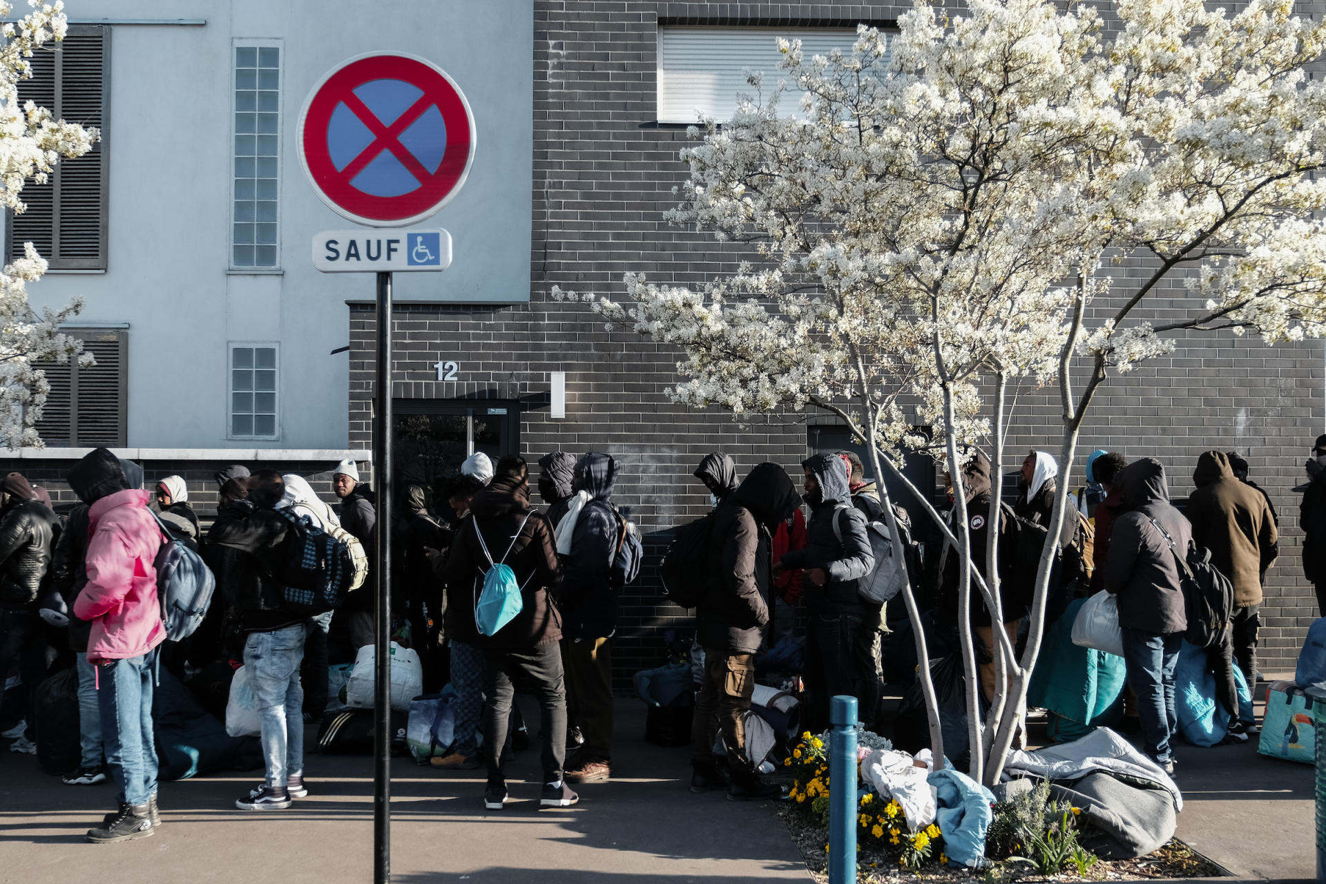 Des migrants du camp d'Auvervilliers attendent en file indienne avant d'être transportés, dans des bus, vers des centres d'hébergement d'urgence.