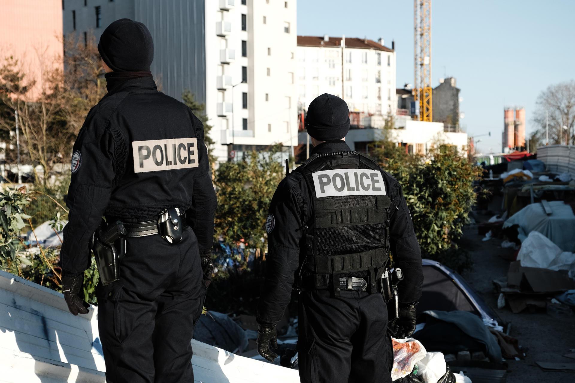 Des policiers accompagnent le déplacement des quelques centaines de migrants qui étaient installés dans le camp de fortune, à Aubervilliers (Seine-Saint-Denis), le 24 mars.