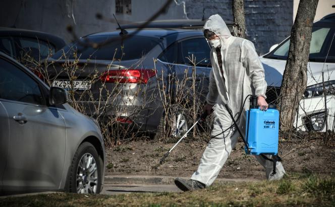 Un employé municipal désinfecte la rue située devant un bloc d'immeubles afin d'éviter la propagation du coronavirus, à Moscou, le 28 mars.