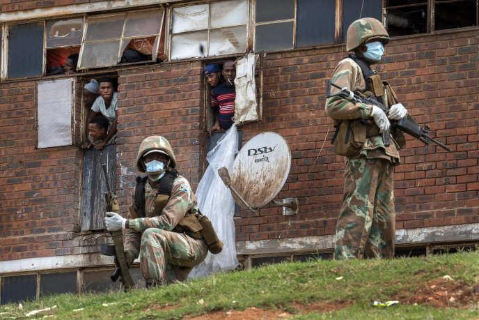 Les forces de défense sud-africaines contrôle le respect du confinement dans le Men's Hostel, township situé à l'est de Johannesburg, le 28 mars.