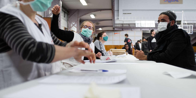 Paris, le 24 mars 2020. Des infirmier.e.s de Médecins Sans Frontières (MSF) accueillent les migrants après leur évacuation du camp d'Aubervilliers (93) dans un gymnanse du 19eme arrondissement. Ils font un premier diagnostic clinique pour indentifier les cas éventuels de Covid 19. Les équipes mobiles de MSF trient les cas suspects présentant des symptômes du Covid 19.