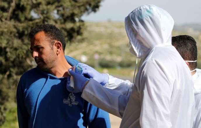 Contrôle de la température d'un travailleur palestinien rentrant d'Israël, près d'Hébron, le 29 mars.