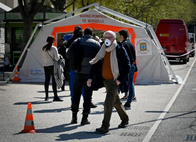 Des patients attendent de se faire tester pour le Covid-19 devant l'institut hospitalier universitaire Meditérranée Infection, à Marseille, le 26 mars.
