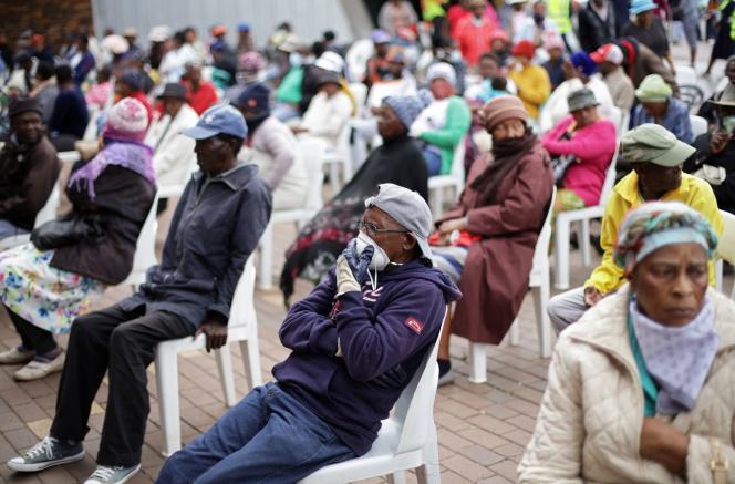 A Soweto, dans la banlieue de Johannesburg, le 30 mars 2020, des personnes âgées font la queue aux guichets assises pour recevoir leur allocation de l'Etat sud-africain.