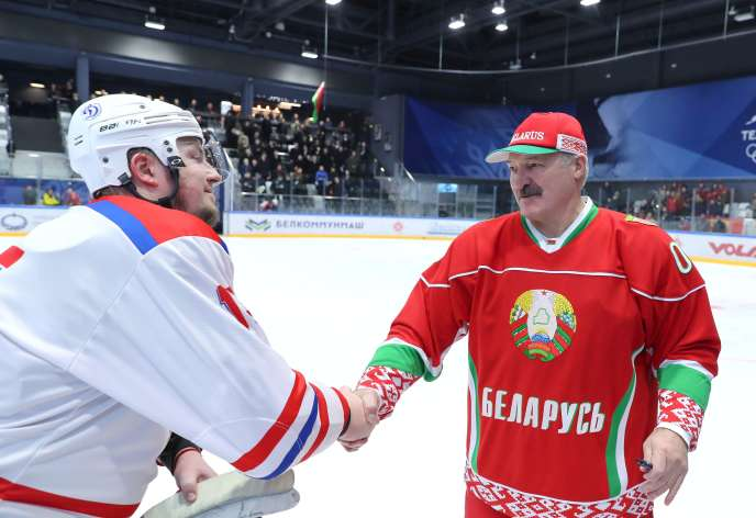 Le président biélorusse Alexandre Loukachenko serre la main d'un joueur de hockey sur glace, à Minsk, le 28 mars.