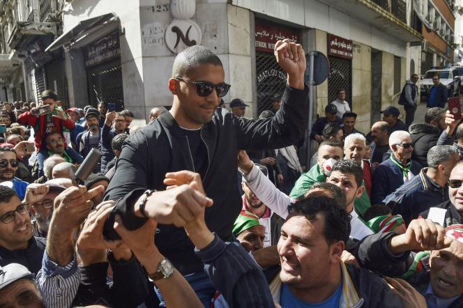 Le 6 mars 2020, à Alger, le journaliste Khaled Drareni est porté sur les épaules de manifestants durant une marche du Hirak.