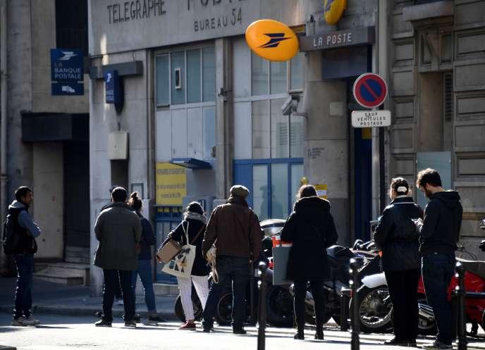 Devant un bureau de Poste, à Paris, le 27 mars 2020.