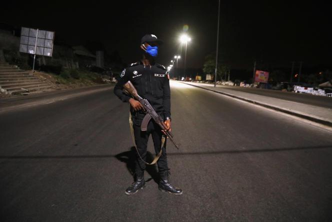Un officier de police monte la garde pendant le couvre-feuà Abidjan, le 28 mars 2020, alors que la Côte d'Ivoire a déclaré l'état d'urgence.