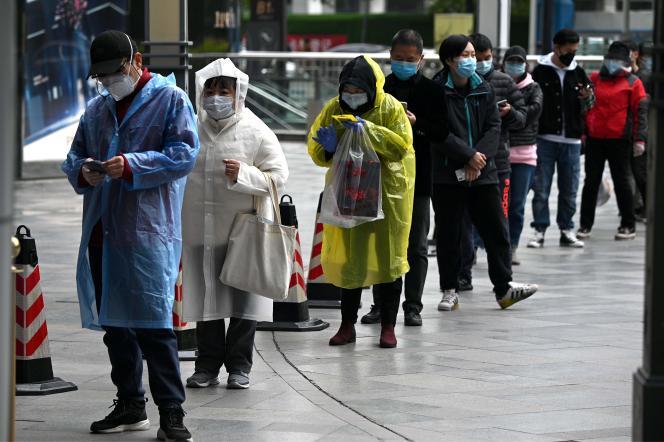 Des gens portant des masques font la queue à l'entrée d'un supermarché de Wuhan, en Chine, le 30 mars 2020.