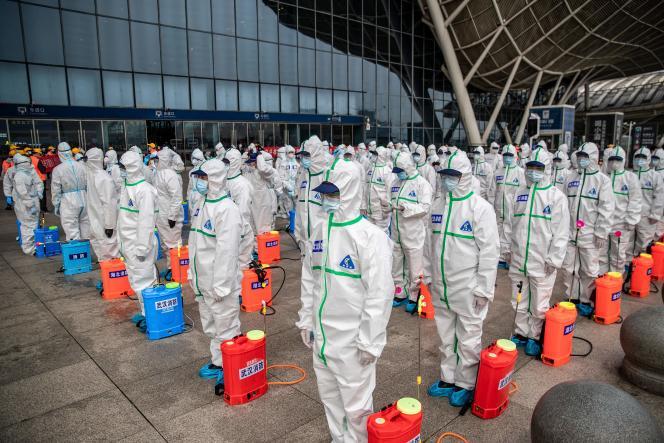 Devant une gare de Wuhan, en Chine, le 24 mars 2020. Les membres d'une équipe de nettoyage se préparent à désinfecter le bâtiment.
