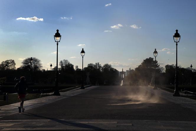 Un homme court à côté du jardin des Tuileries, fermé, à Paris, le 30 mars.